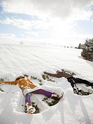 Orem, Utah, USA, young couple making snow angels