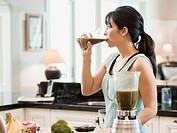 USA, Utah, Alpine, mid adult woman standing in kitchen and drinking cocktail