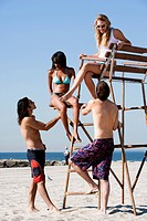 WR0932495 Four adults at the beach with a lifeguard chair