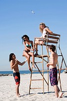 WR0932499 Four adults at the beach with a lifeguard chair