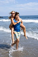 WR0932748 Man carrying woman through shallow water at the beach