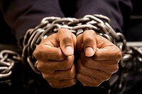 Businessmans hands bound in chains