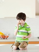 USA, Utah, Boy 4_5 eating kiwi in kitchen