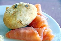 Slices of salmon fume and bread roll on plate