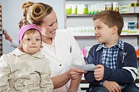 Druggist with children in conversation,