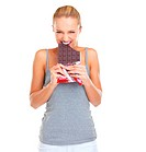 Expressive and gleeful young woman biting into a slab of chocolate