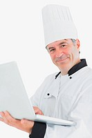 Happy male chef using laptop