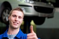 Car mechanic gesturing thumbs up
