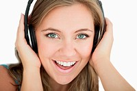 Close_up of young woman listening music through headphones