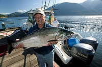 Sportfishermen holding Coho Salmon, Port Alice, Northern Vancouver Island, British Columbia, Canada