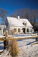 Old Canadiana cottage style residential home in winter, Quebec, Canada