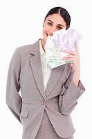 Portrait of happy business woman holding fanned banknotes
