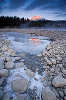 Pyramid Mountain reflected in partly frozen pool at sunrise, Jasper National Park, Alberta, Canada
