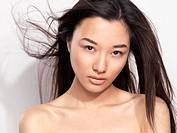 Closeup beauty portrait of a young asian woman face with flying hair
