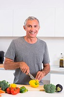 Smiling man cutting a yellow pepper
