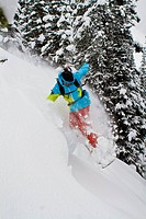A man drops his splitboard off a pillow while touring at Icefall Lodge, Golden, BC