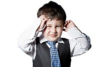 Child dressed like businessman with hands on his face funny
