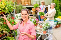 Woman buying potted flower in garden shop