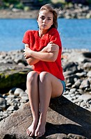 girl badly frozen sitting on a rock