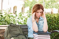 Female Student Outside with Headache Sitting