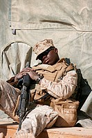 A U.S. Marine sleeps while waiting for a helicopter flight at Camp Bastion, Helmand Province, Afghanistan.