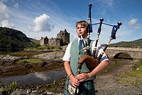 Young bagpiper in front of Eilean Donan Castle at Loch Duich, near Dornie, Highland, Scotland, United Kingdom