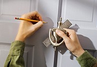 man attaching door knocker to door