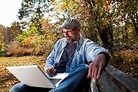 Mature man using laptop outdoors