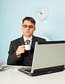 Serious man at office with laptop and cup of coffee