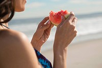 Woman eating watermelon at beach