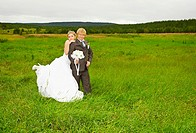 Bride and groom on nature in field