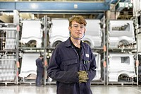 Apprentice standing in car factory