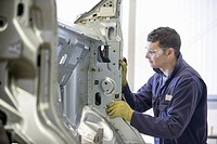 Apprentice working in car factory