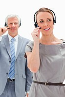 Close_up of a woman wearing a headset with a white hair businessman