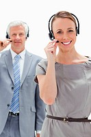 Close_up of a woman smiling and wearing a headset with a white hair businessman