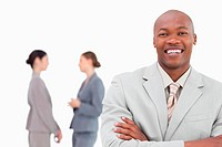 Smiling businessman with folded arms and co_workers behind him