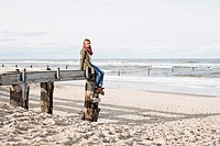 Woman on abandoned pier on beach