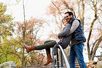 Couple hugging over park railing