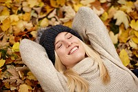 Woman laying in autumn leaves outdoors