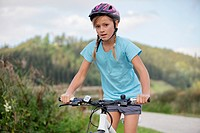 Girl riding bicycle on rural path