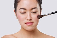 Close_up of young woman applying blush over white background