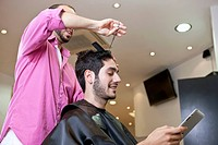 A male client looking at a digital tablet whilst having his hair cut