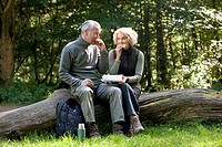 A mature couple sitting on a tree trunk eating a packed lunch
