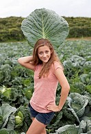 Girl posing with a large cabbage leaf