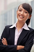 Smiling Chinese businesswoman with arms crossed