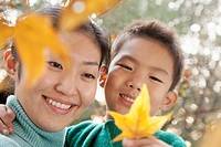 Chinese mother and son looking at autumn leaf