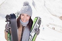 Chinese woman standing on ski slope with skis
