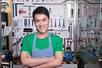 Chinese man with arms crossed standing in workshop