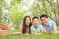 Chinese family laying in grass in park