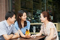 Chinese friends having wine at cafe